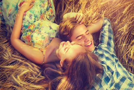 adorar: Pares felizes que relaxam ao ar livre no campo de trigo, conceito do amor