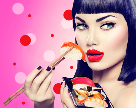 sushi restaurant: Beauty model girl eating nigiri sushi with chopsticks