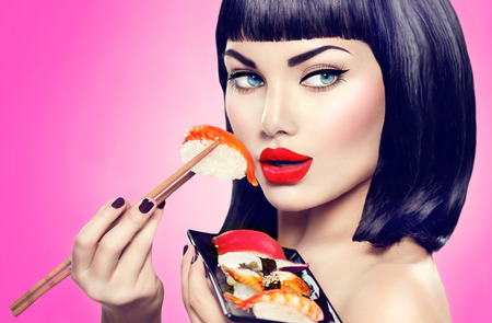 Beauty model girl eating nigiri sushi with chopsticks