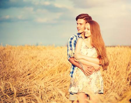 parejas jovenes: Feliz pareja bes�ndose y abraz�ndose al aire libre en campo de trigo, el concepto de amor