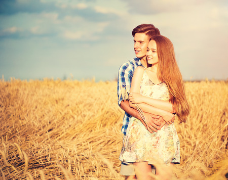 young boy smiling: Happy couple kissing and hugging outdoors on wheat field, love concept