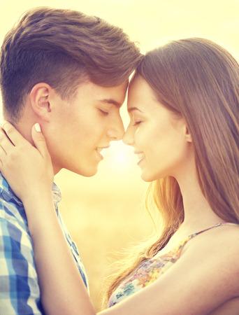 jovenes felices: Feliz pareja bes�ndose y abraz�ndose al aire libre en campo de trigo, el concepto de amor