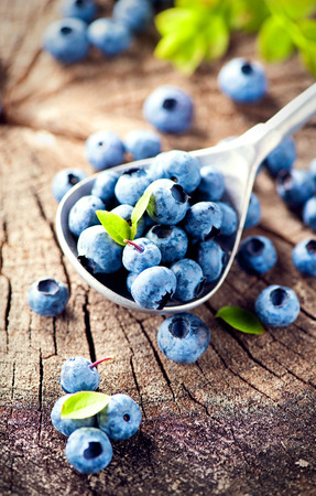 is cultivated: Blueberry on wooden background. Ripe and juicy fresh picked blueberries closeup