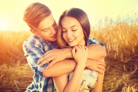 parejas de amor: Feliz pareja bes�ndose y abraz�ndose al aire libre en campo de trigo, el concepto de amor