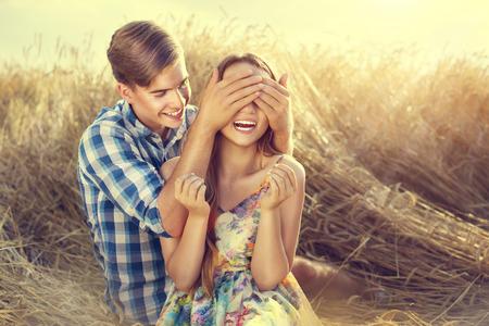 bacio: Coppie felici che hanno divertimento all'aperto sul campo di grano, il concetto di amore