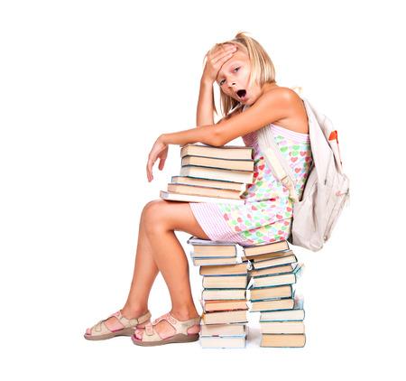 colegiala: De vuelta a la escuela. Cansado Colegiala sentado sobre una pila de libros Foto de archivo