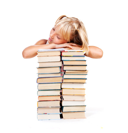 Back to school. Tired Schoolgirl sleeping on a stack of books Stock Photo
