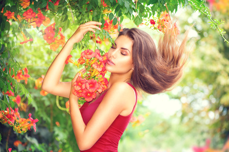 creeper: Beauty model girl enjoying nature in garden with beautiful tropical flowers