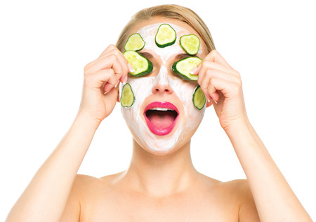 Spa woman applying fresh facial mask with cucumbers