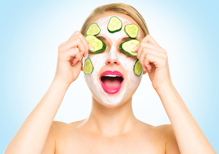 Funny spa woman applying fresh facial mask with cucumbers