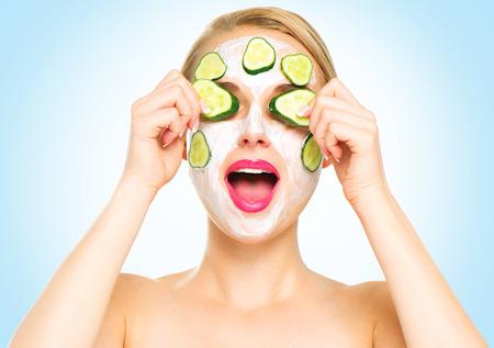 masaje facial: Mujer del balneario divertido aplica la máscara facial fresca con pepinos