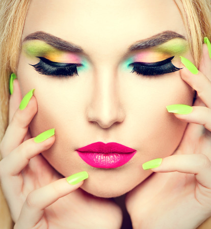 Beauty woman portrait with vivid makeup and colorful nail polish