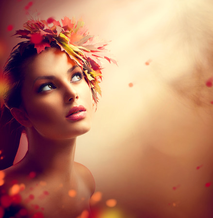 ojos marrones: Chica otoño romántico con coloridas hojas amarillas y rojas en la cabeza Foto de archivo
