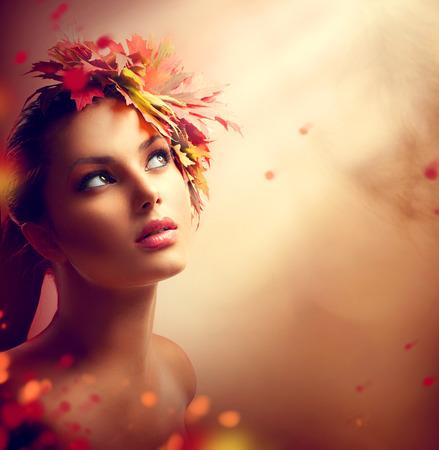 belle brune: Romantique fille automne avec les feuilles jaunes et rouges color�s sur la t�te Banque d'images