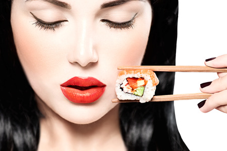Fashion art portrait of beauty model girl eating sushi roll