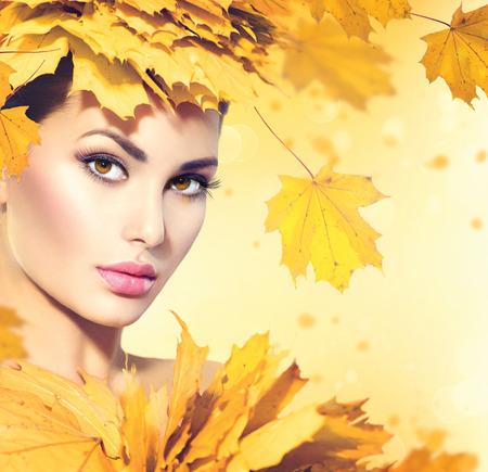 Mujer del otoño con las hojas amarillas estilo de pelo