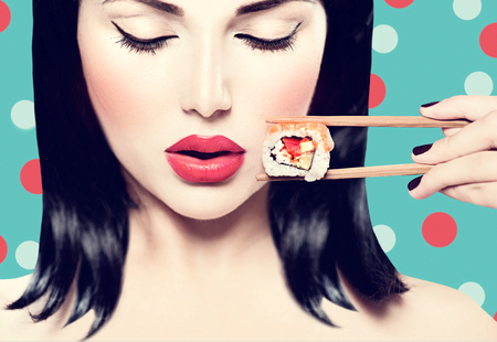 people eating restaurant: Beautiful woman holding chopsticks with sushi roll Stock Photo