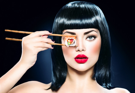 Beautiful woman holding chopsticks with sushi roll Imagens
