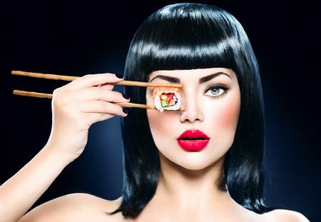 personas comiendo: Mujer que sostiene los palillos hermosas con rollo de sushi Foto de archivo