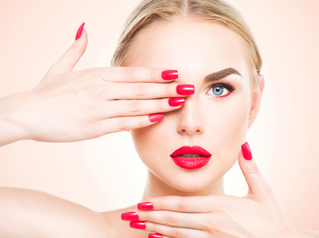 Beautiful woman with blond hair. Fashion model with red lipstick and red nails. Portrait of glamour girl with bright makeup. Beauty female face. Perfect skin and make up close up Stockfoto