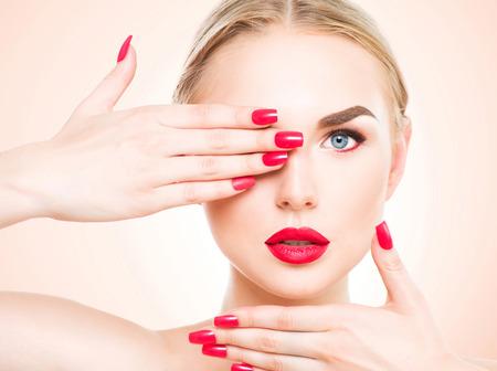 Vacker kvinna med blont hår. Modell med rött läppstift och röda naglar. Porträtt av glamour flicka med ljusa makeup. Skönhet kvinnligt ansikte. Perfekt hud och make up närbild Stockfoto