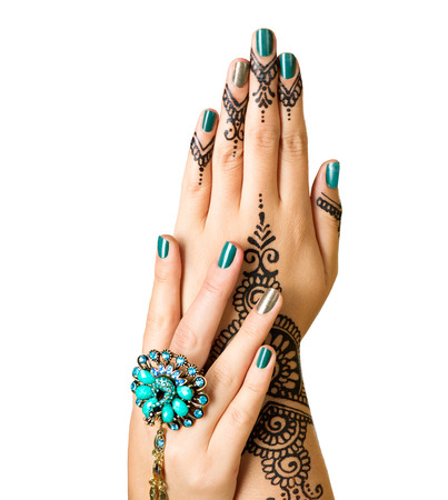Mehndi tattoo isolated on white. Woman Hands with black henna tattoos. Hands of Indian bride girl with mehndi and perfect emerald manicure and emerald Indian jewels. India national traditions