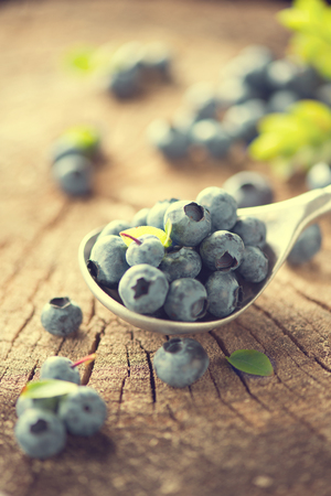 wood agricultural: Blueberry in spoon on wooden table background. Ripe and juicy fresh picked bilberries closeup on Weathered Wood Boards for a Vintage Look. Blueberries close up. Vertical photo Stock Photo