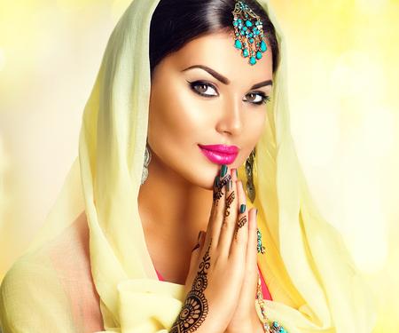 Schoonheid Indisch meisje met mehndi tatoeages houden handpalmen tegen elkaar. Mooie Hindoe exotische vrouw in sari en smaragd oosterse juwelen in de camera kijken. India. Tradities begrip Stockfoto