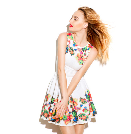 Fashion photo of young magnificent woman. Beautiful blonde girl posing in studio. Model wearing a summer dress with floral print. Perfect make-up and manicure. Romantic style
