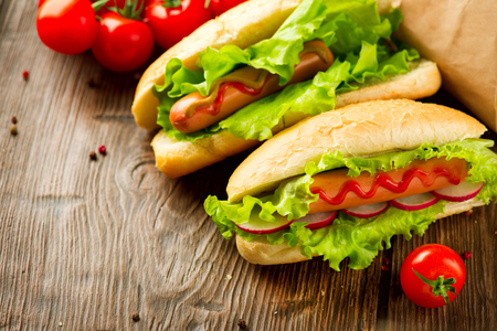 hotdog: Classic Hot dogs close-up. Big Grilled hot dogs with sausage, lettuce and radish served with ketchup sauce on dark wooden table. Homemade tasty meal. Food concept. Sandwich Stock Photo