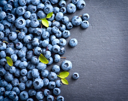 bilberries: Blueberries background. Blueberry border design. Ripe and juicy fresh picked bilberries close up. Copyspace for your text