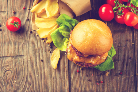 Tasty burger with fried juicy beef patties and fresh tomatoes with lettuce over wooden table. Hamburger with vegetables close-up. Cheeseburger with fried potatoes on rustic surface. Vintage style