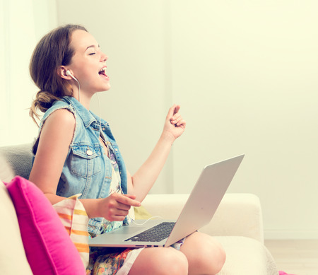 Beautiful teenage girl sitting on sofa at home, using laptop computer, laughing and having fun. Happy Teenage girl enjoying the music with headphones and dancing. Emotions. Happiness. Good mood