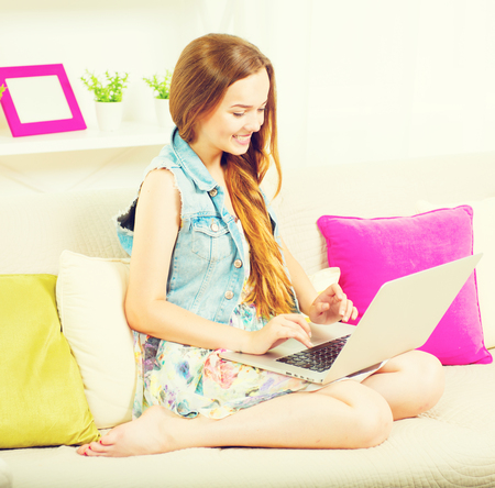 laptop home: Pretty teenage girl sitting on sofa at home with laptop. Happy Girl with long hear typing on laptop and smiled. Teenage girl using laptop computer Stock Photo