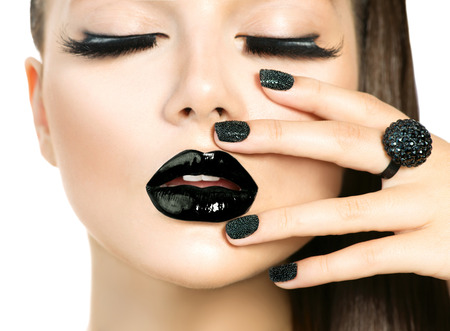 Mujer hermosa del modelo de manera con las pestañas largas y Negro compone aislado en blanco. Moda moda Caviar Manicure Negro. Arte de uñas. Oscuro Lápiz labial y esmalte de uñas. Estilo de Vogue Foto de archivo