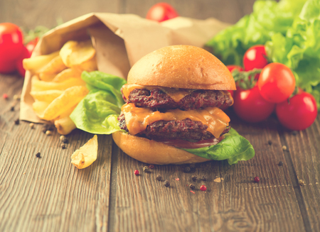 junk: Fast food concept. Junk food over dark wooden table. Vintage style hamburger with fries and vegetables on rustic wooden table served with French Fries in crumpled brown paper. Homemade food
