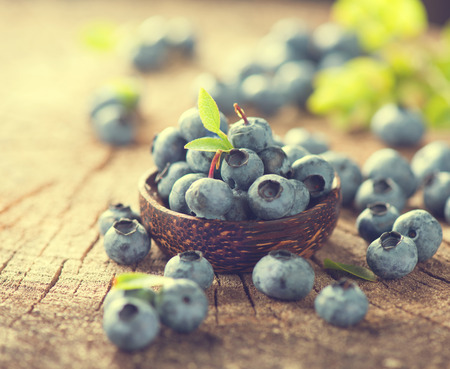 bilberries: Freshly picked Blueberries in bowl on wooden table. Blueberry closeup. Concept of healthy eating. Bilberries in Vintage toned