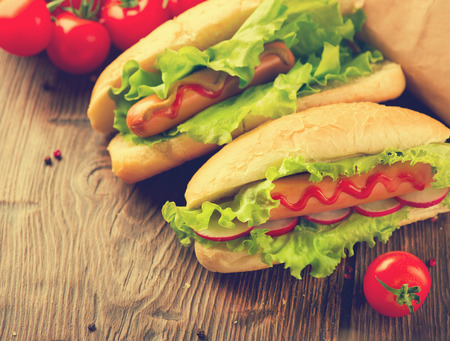 rustic food: Beauty Hot dogs close up. Two Big hot dogs with salad ingredients on rustic wooden background. Vintage style. Homemade food. Sandwiches