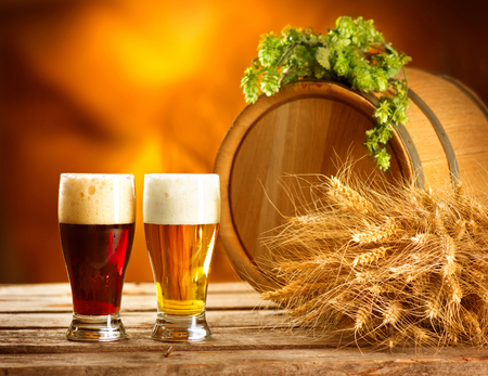 beer in bar: Still life composition with Vintage beer barrel and two glasses of dark and light beer. Fresh amber beer concept. Green corns of hop and wheat on wooden table. Ingredients for brewery. Brewing traditions