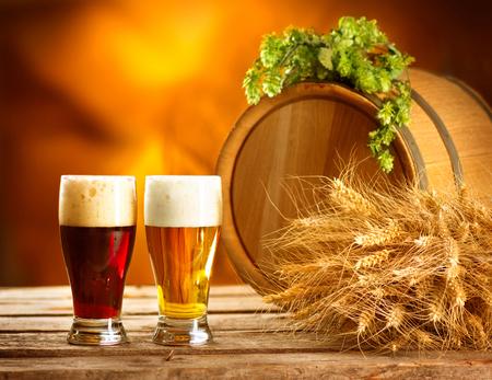 cerveza: Todavía composición de la vida con el barril de cerveza de la vendimia y dos vasos de cerveza oscura y la luz. Fresh concepto cerveza ámbar. Granos verdes de lúpulo y trigo en la mesa de madera. Ingredientes para la cervecería. Tradiciones cerveceras