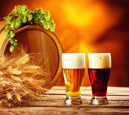 伝統: ビール樽と緑のホップと木製のテーブルのムギの耳を 2 つのビールのグラス。闇と光のビール。醸造所のコンセプトです。醸造の伝統