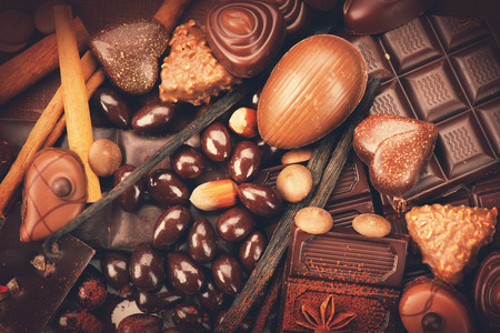 candy border: Luxury chocolate close up. Candies Chocolate vintage style. Delicious assortment of white, dark, milk chocolate bonbon with nuts, vanilla and cinnamon. Belgium chocolate Stock Photo