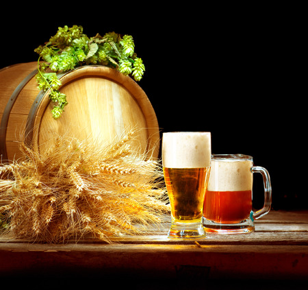 Vintage barrel and glasses full of fresh beer with hop cones and wheat of ears on wooden table isolated over black background. Brewing traditions. Ingredients for beer. Brewery concept Stock Photo