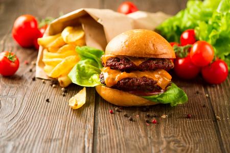 소박한 나무 표면에 튀긴 감자와 육즙과 향기로운 햄버거. 맛있는 빵과 신선한 야채와 함께 수분이 충족 돈까스와 치즈 어두운 나무 테이블에 감자 튀