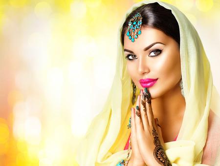 결혼식: 아름다움 인도 여성의 초상화입니다. 힌두교 소녀 상태에서 손을 함께 기호기도와 감사합니다. 블랙 헤나 문신이 카메라를 찾고 인도 모델 소녀. 멘디.