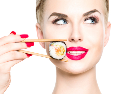 Beautiful blonde girl eating sushi close-up isolated on white. Smiled woman with perfect make up and red lips holding Sushi roll with chopsticks. Healthy Japanese food. Diet concept