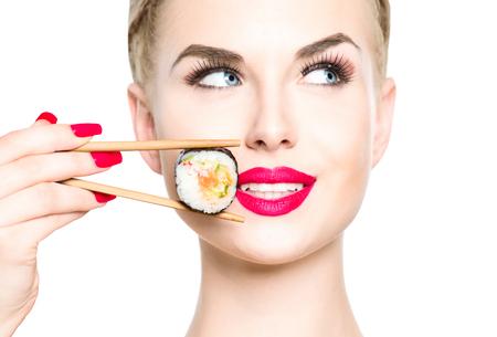 La muchacha rubia hermosa comer sushi close-up aislados en blanco. Mujer sonrió con perfecto maquillaje y labios rojos sosteniendo rollo de sushi con los palillos. Comida japonesa sana. Concepto de la dieta