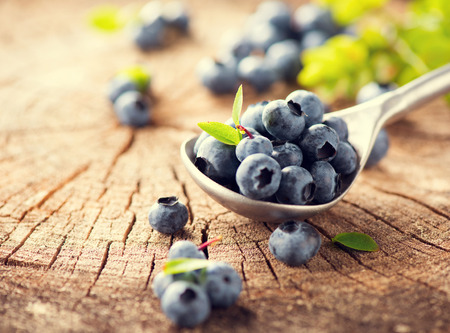 Blueberries in bowl over wooden background. Blueberry close-up on cracked surface. Concept of healthy diet. Freshly picked Bilberries with leaves. Harvest concept