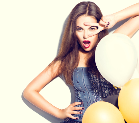 Beautiful fashion model girl with colorful balloons posing over white
