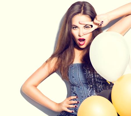 moda: Piękna modelka dziewczyna z kolorowych balonów stwarzających nad białym